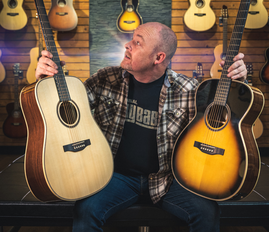 Billy Finlayson holding two guitars